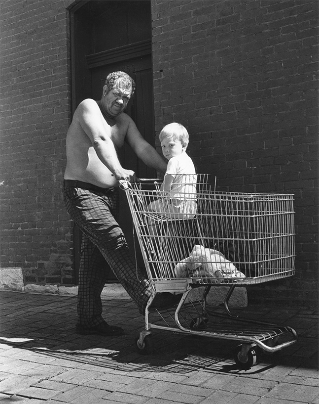 Unknown Man with Child in Shopping Cart